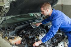 Male mechanic with digital tablet repairing car engine
