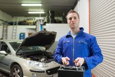 Portrait of male mechanic carrying car battery in workshop